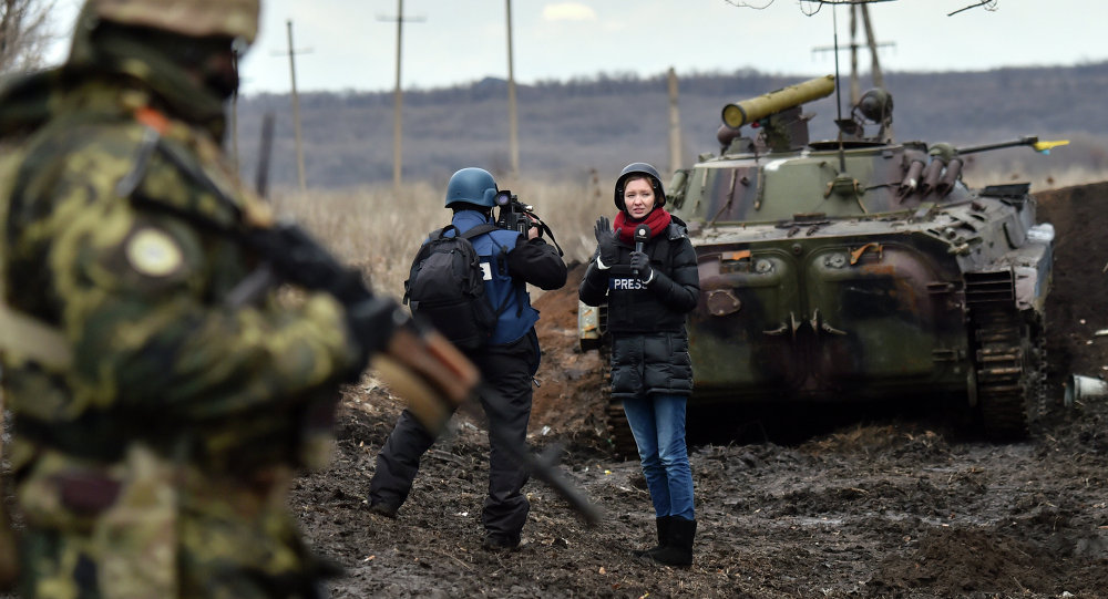 A TV journalist prepares to do a piece to camera in front of an armoured personnel carrier (APC) on the frontline between Ukrainian forces and militants near the eastern Ukrainian city of Debaltseve, in the Donetsk region