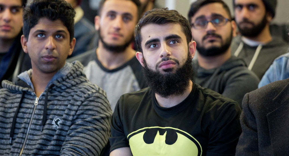 Students at Queens College in New York gather for a vigil, Wednesday, Feb. 18, 2015, in honor of three Muslim students killed recently near the University of North Carolina