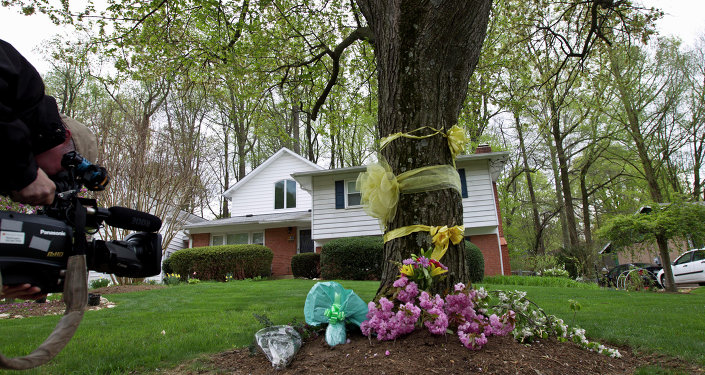 A cameraman photographs flowers and ribbon on a tree outside Weinstein family house in Rockville, Md., Thursday, April 23, 2015
