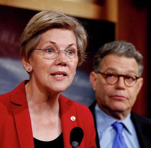 Sen. Elizabeth Warren, D-Mass, left, speaks at a new conference on Capitol Hill in Washington.