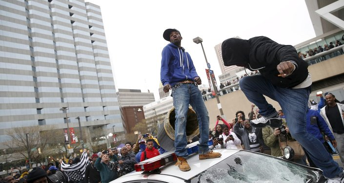 Protesters jump on a police car at a rally to protest the death of Freddie Gray who died following an arrest in Baltimore, Maryland April 25, 2015