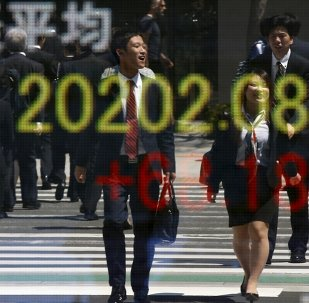 People are reflected in an electronic board displaying Japan's Nikkei share average outside a brokerage in Tokyo April 23, 2015