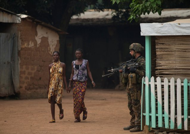 Girls hold hands as they walk past a French soldier holding a position, during an operation to secure part of the Miskine neighborhood, in Bangui, Central African Republic, Thursday, Dec. 26, 2013