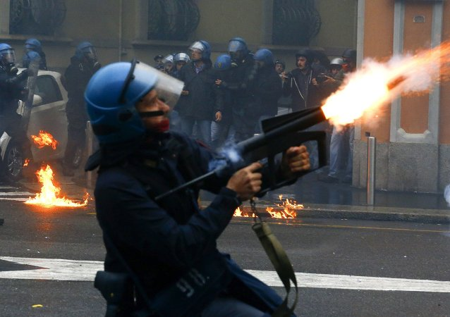 A policeman fires tear gas during a rally against Expo 2015 in Milan, Italy, May 1, 2015