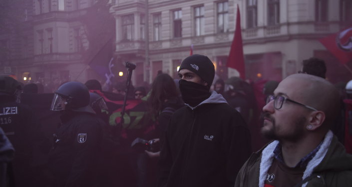 A protester wears a mask while flares are used during the 'Revolutionary' May Day demonstration in Berlin on May 1, 2015.