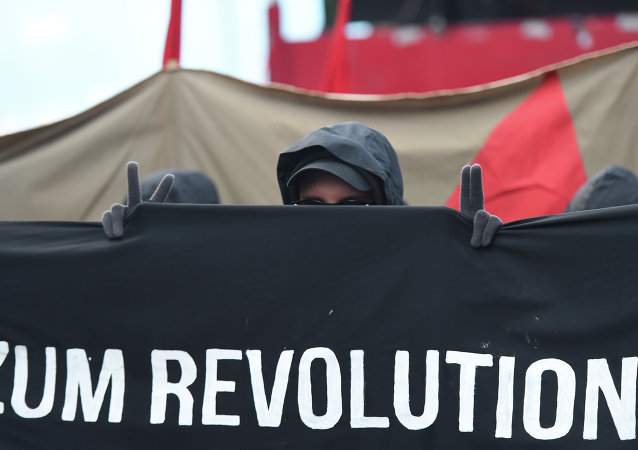 A protester shows the victory sign as he marches with a banner promoting a social revolution worldwide as he takes part in the 'Revolutionary' May Day demonstration in Berlin on May 1, 2015.