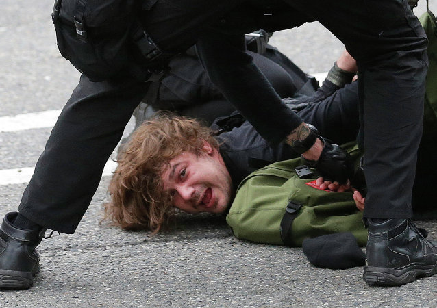 Police officers arrest a man during a May Day anti-capitalism march, Friday, May 1, 2015 in Seattle.