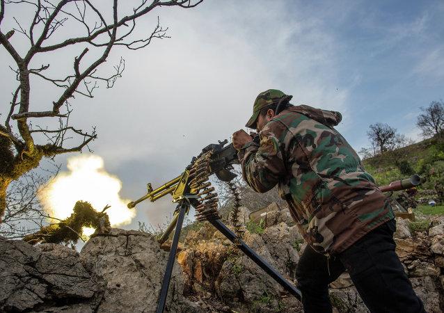 Военнослужащий правительственной армии Сирии ведет огонь из пулемета на позиции войск на одной из вершин возле города Кесаб