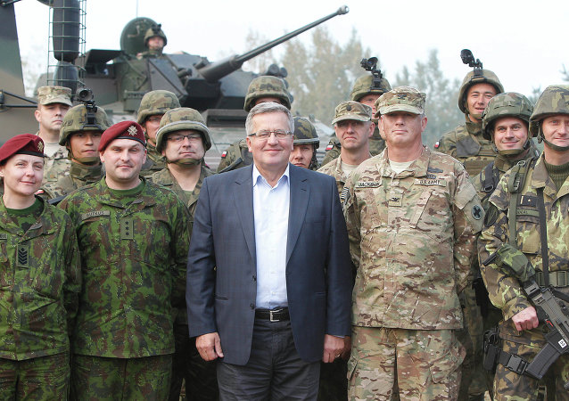 Poland's President Bronislaw Komorowski stands with troops from Poland and other nations in Bemowo Piskie near Orzysz, in northeastern Poland