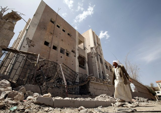 A man looks at a school destroyed by an air strike as he flees his home in Sanaa April 28, 2015