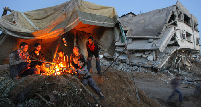 Palestinians sit around a fire under the cover of a tent on the ruins of their home