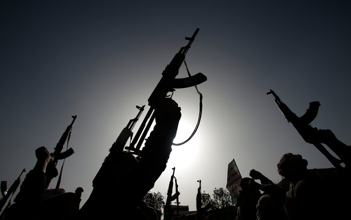 Shiite rebels known as Houthis hold up their weapons to denounce the Saudi-led airstrikes as they chant slogans during a protest in Sanaa, Yemen