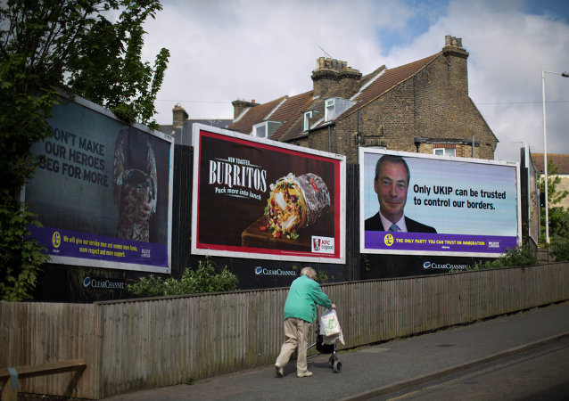 A woman walks past a UK Independence Party (UKIP) election poster showing their leader Nigel Farage in Ramsgate, south east England, Thursday, May 7, 2015