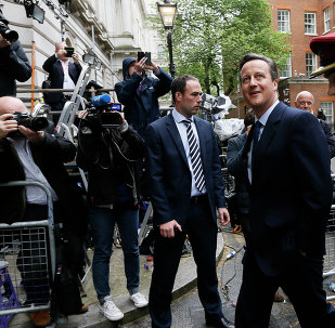 Britain's Prime Minister David Cameron, left, leaves 10 Downing Street in London with a soldier, to attend a VE Day service at the Cenotaph, Friday, May 8, 2015