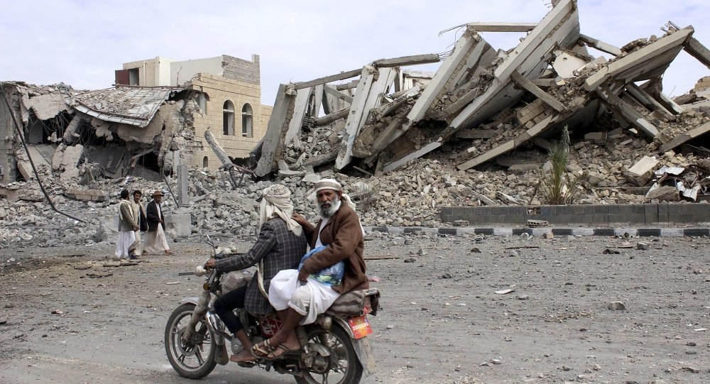 People ride on a motorcycle as they pass by a police headquarters destroyed by a Saudi-led air strike in Yemen's northwestern city of Saada May 7, 2015