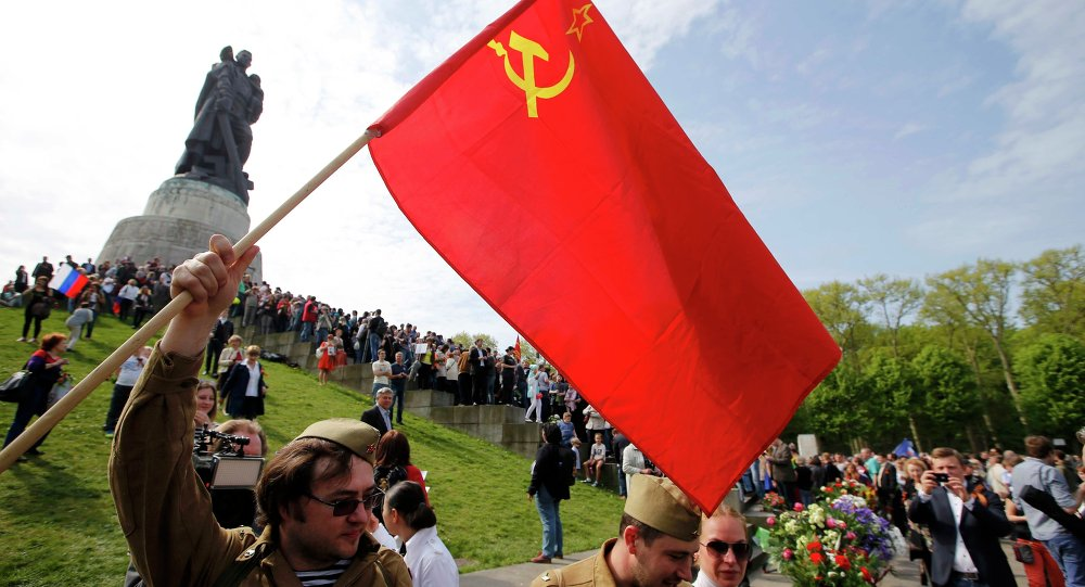 A man wearing an old uniform holds a Soviet flag during celebrations to mark Victory Day, at the Soviet War Memorial in Treptower Park in Berlin, Germany, May 9, 2015