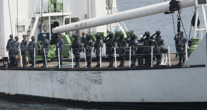 The Philippine Coast Guard personnel salute coast guard officials following a combined maritime exercise by Philippine and Japanese Coast Guards.