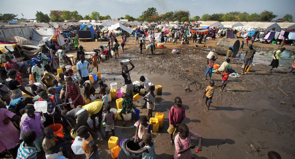 In this file photo of Sunday Dec. 29, 2013 file photo, displaced people gather around a water truck to fill containers at a United Nations compound which has become home to thousands of people displaced by the recent fighting, in the capital Juba, South Sudan