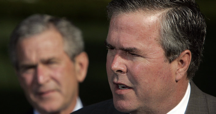 George W. Bush (L) looks on as his brother  Jeb Bush