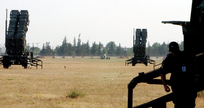 An air force radar operator inspects equipment in front of a Patriot missile launcher at Tatoi air base, near Athens