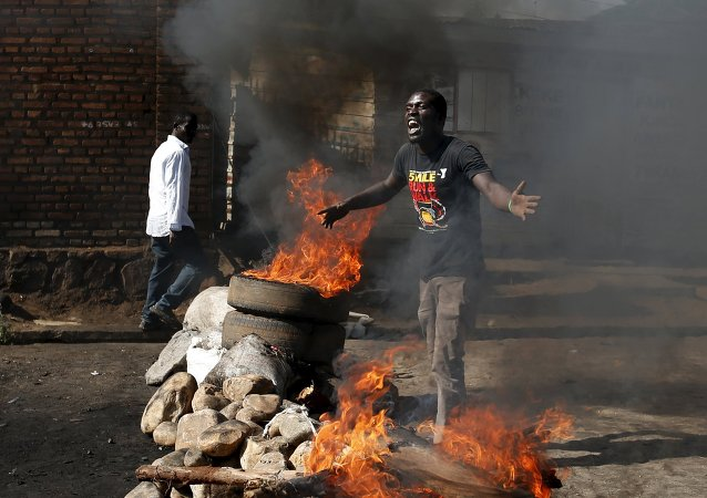 A protester, who is against President Pierre Nkurunziza's decision to run for a third term, gestures in front of a burning barricade in Bujumbura, Burundi May 14, 2015