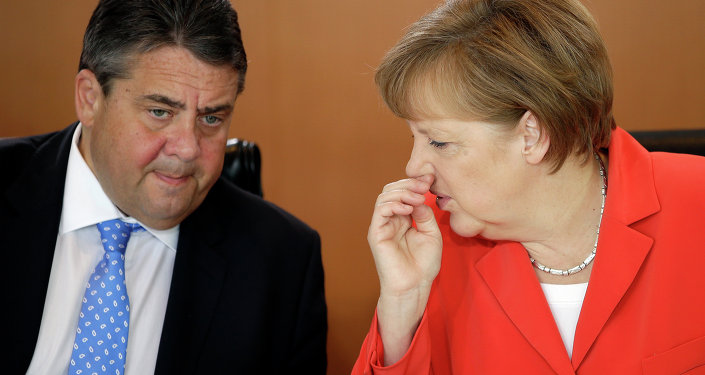German Chancellor Angela Merkel speaks to the Vice-Chancellor Sigmar Gabriel.