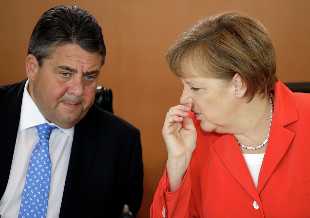 German Chancellor Angela Merkel speaks to the Vice-Chancellor Sigmar Gabriel.