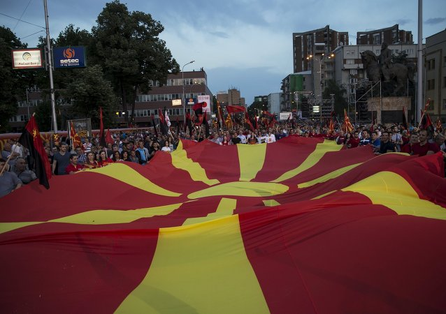 Supporters of the ruling VMRO-DPMNE party and Prime Minister Nikola Gruevski hold a Macedonian flag during a rally in Skopje, Macedonia, May 18, 2015