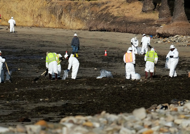 Clean up crews remove oil-laden sand on the beach at Refugio State Beach, site of an oil spill.