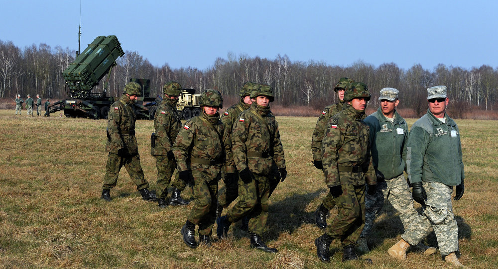 Polish soldiers watch as US troops from the 5th Battalion of the 7th Air Defense Regiment emplace a launching station of the Patriot air and missile defence system at a test range in Sochaczew, Poland