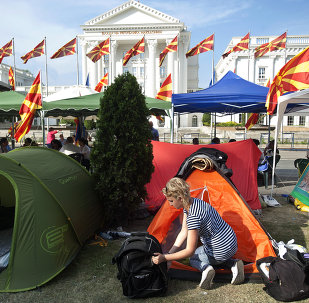 A woman stands next to her tent in a makeshift camp in front of the government building where protesters have said they will not leave until the government resigns, in Skopje