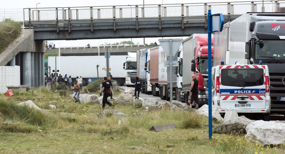 Policemen stand guard next to truck queuing to board a ferry to Great Britain to prevent migrants to reach the UK illegally, on September 10, 2014 in the French port of Calais. File Photo