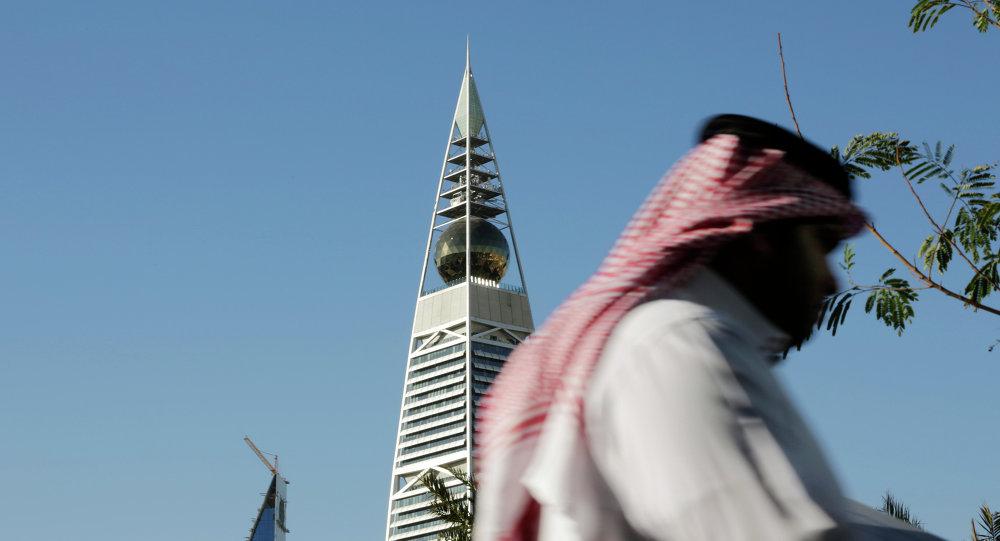 A Saudi man passes the al-Faisaliya tower in Riyadh, Saudi Arabia.