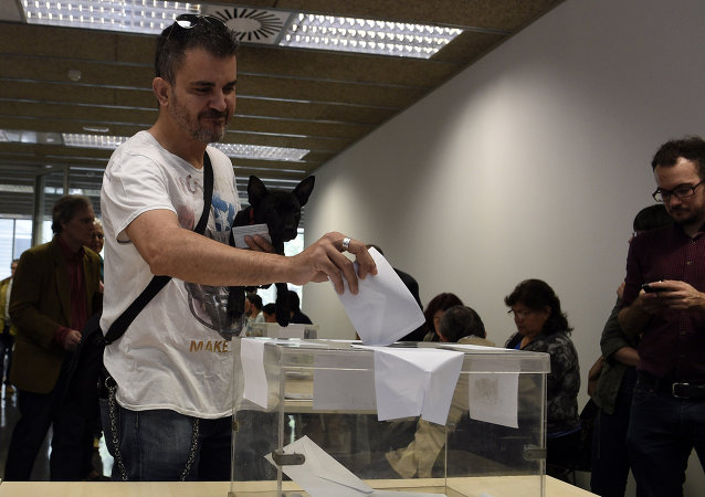 A man carrying a dog casts his ballots in the Spain's municipal and regional elections at a polling station in Barcelona on May 24, 2015