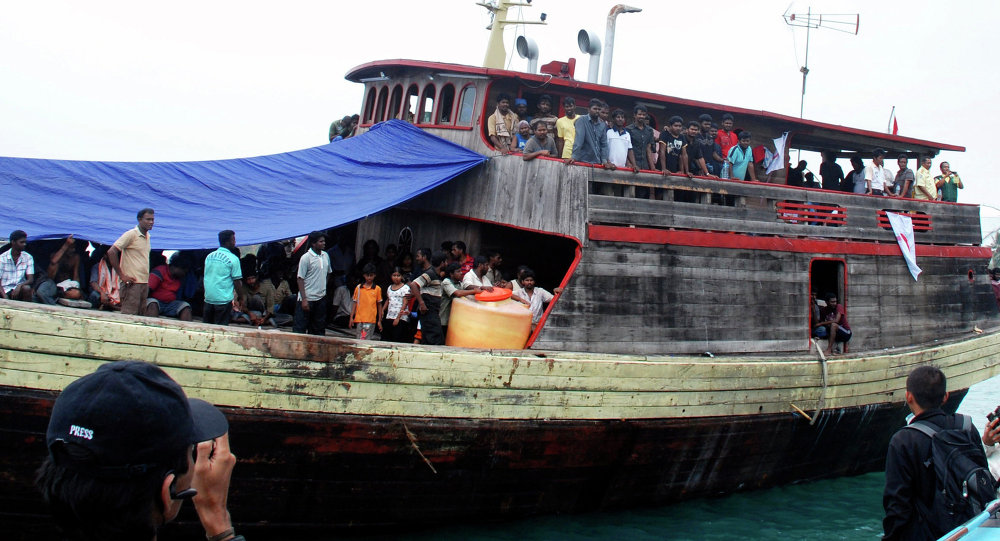 Sri Lankan migrants are seen on board of a wooden boat as they dock at a port in Cilegon, Banten province, Indonesia, Monday, Oct. 12, 2009