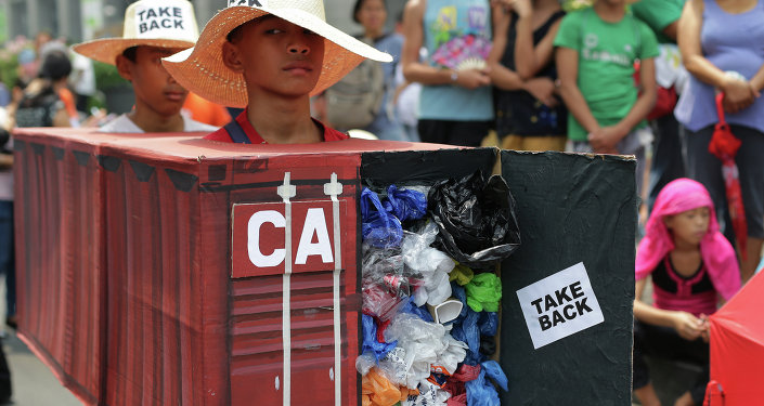 Filipino environmental activists wear a mock container vans filled with garbage to symbolize the 50 containers of waste that were shipped from Canada to the Philippines two years ago, as they hold a protest outside the Canadian embassy at the financial district of Makati, south of Manila, Philippines on Thursday, May 7, 2015