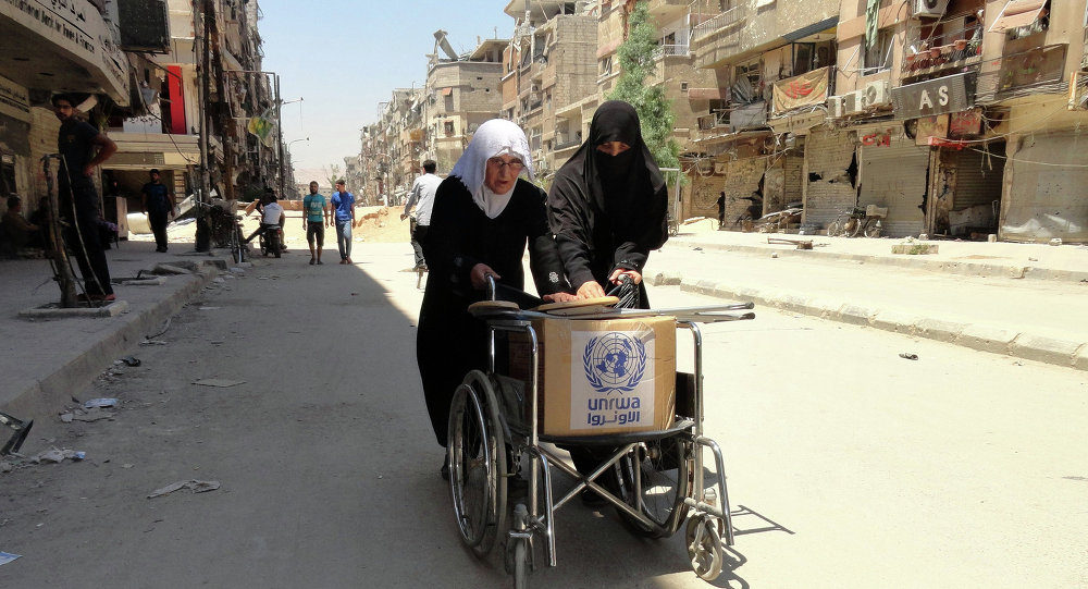 Residents of Syria's Yarmuk Palestinian refugee camp, south of Damascus, use a wheelchair to carry a box of goods distributed by the United Nations Relief and Works Agency (UNRWA) on July 17, 2014