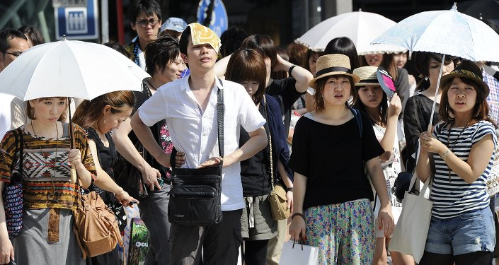 People wait for a green light at a crossing as they use umbrellas and hats to shade themselves from the sunshine in Tokyo.