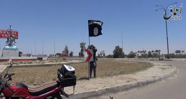 An image grab taken from a video uploaded on May 18, 2015 by Aamaq News Agency, a Youtube channel which posts videos from areas under the Islamic State (IS) group's control, allegedly shows an IS fighter hanging a flag of the group in a street of Ramadi, the Iraqi capital of Anbar province, a day after the city was captured by IS