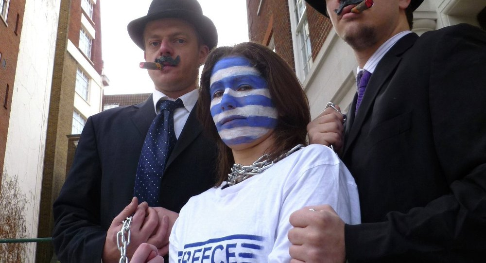 Campaigners dressed as bankers hold Greece in chains outside the European Commission in London.