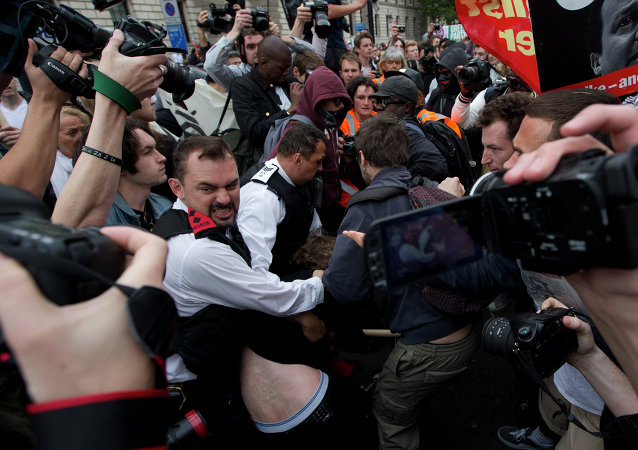 A demonstrator is held by two police officers surrounded by other protesters and members of the media during an anti-austerity, anti-Conservative Party protest after the Queen's Speech was delivered to Parliament in London, Wednesday, May 27, 2015.