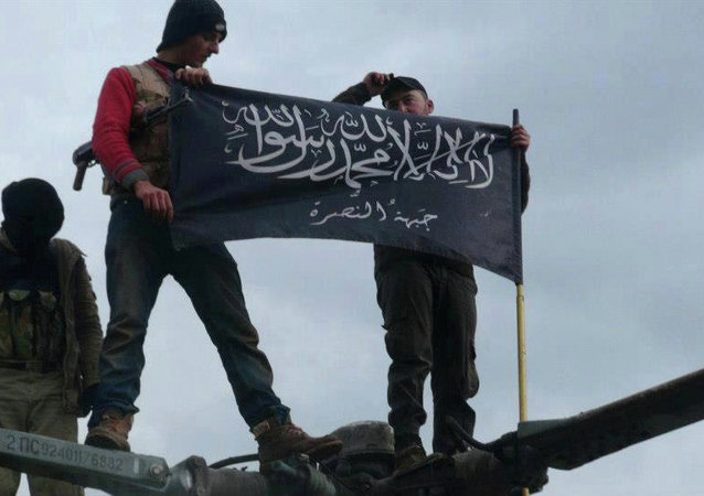 Rebels from al-Qaida-affiliated Jabhat al-Nusra, also known as the Nusra Front, wave their brigade flag, as they step on the top of a Syrian air force helicopter.
