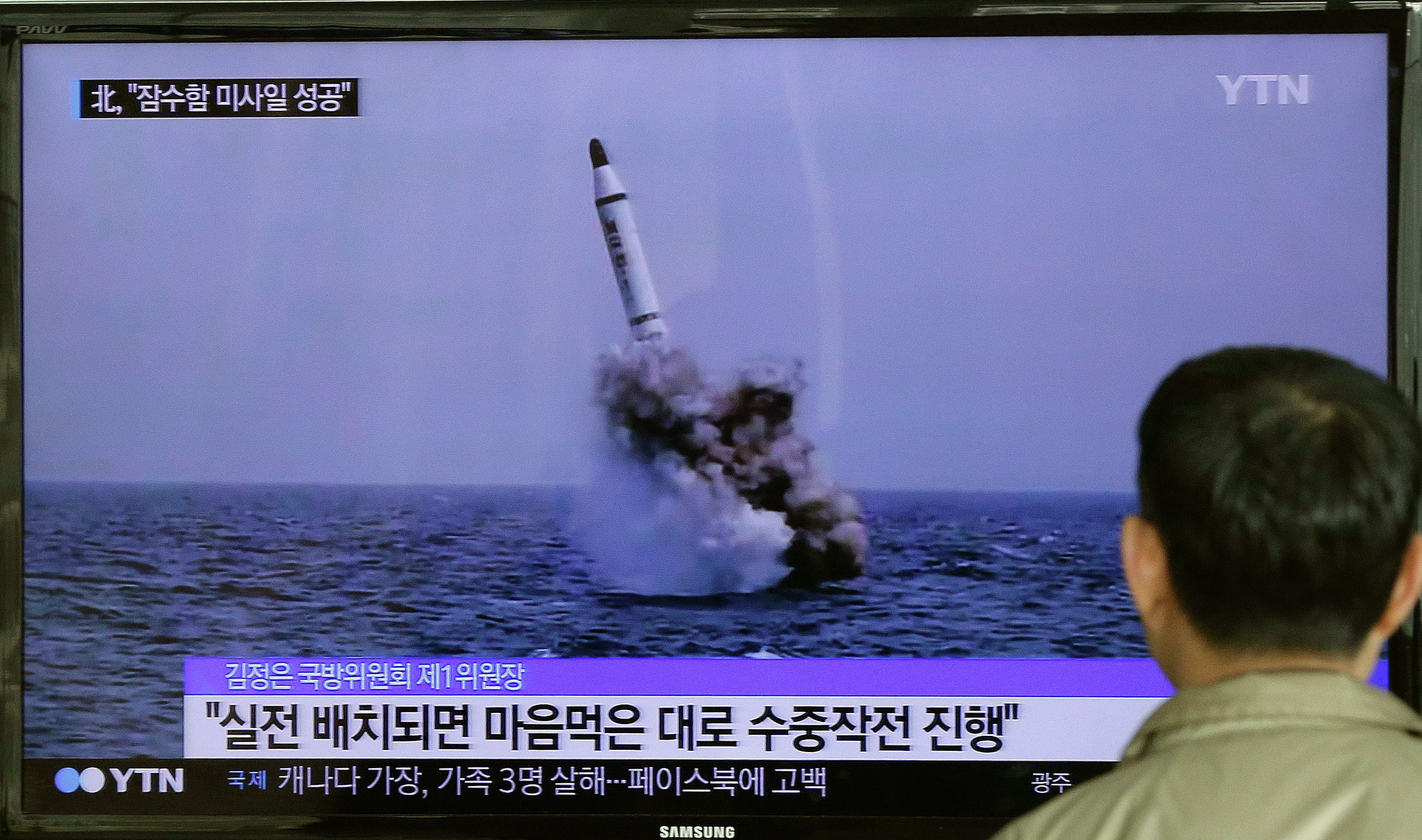 A South Korean man watches a TV news program showing an image published in North Korea's Rodong Sinmun newspaper of North Korea's ballistic missile believed to have been launched from underwater, at Seoul Railway station in Seoul, South Korea, Saturday, May 9, 2015