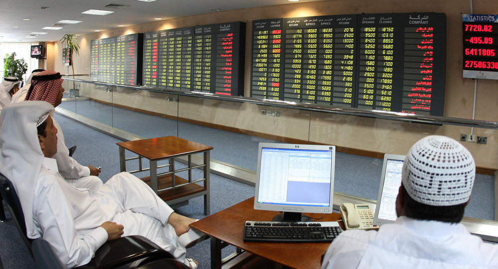 Investors follow the stock market activity on monitors at the Doha Securities Market