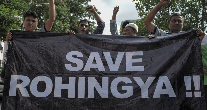 Ethnic Rohingya refugees from Myanmar residing in Malaysia hold a banner during a protest outside the Myanmar embassy in Kuala Lumpur on May 21, 2015
