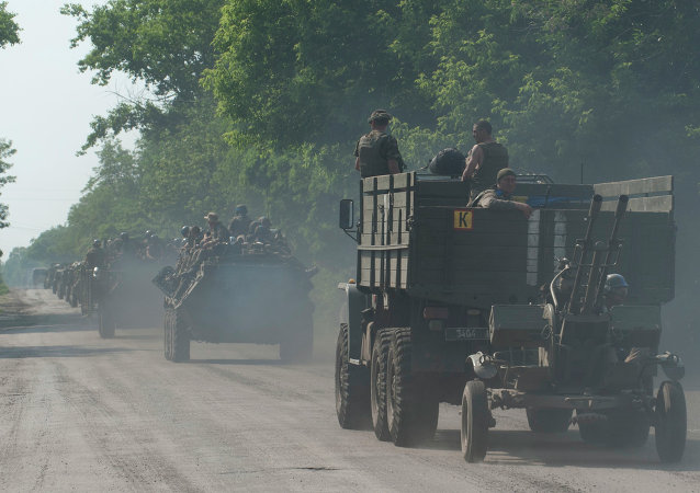 A convoy of Ukrainian military vehicles drive on the outskirts of Marinka, Donetsk region, eastern Ukraine, Thursday, June 4, 2015.
