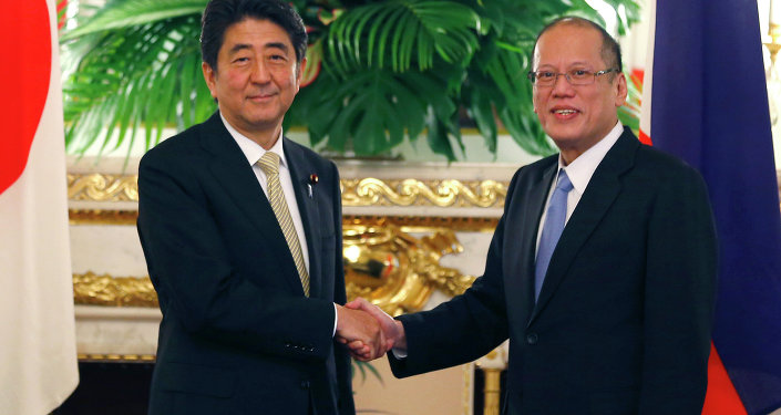 Philippine President Benigno Aquino III, right, shakes hands with Japanese Prime Minister Shinzo Abe.