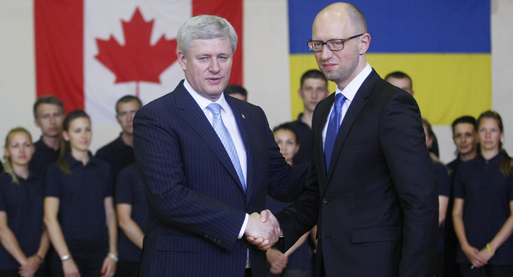 Ukrainian Prime Minister Arseniy Yatsenyuk (R) welcomes his Canadian counterpart Stephen Harper during their meeting in Kiev