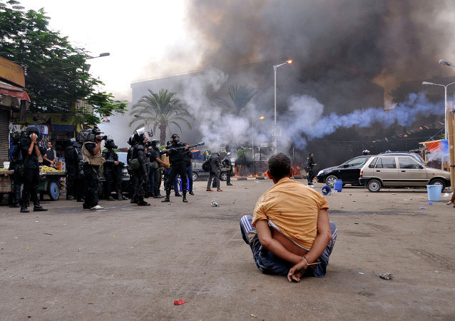 A handcuffed protester sits on the ground as Egyptian security forces move in to disperse supporters of Egypt's ousted president Mohamed Morsi by force in a huge camp in Cairo's Al-Nahda square on August 14, 2013