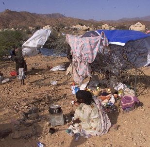 Internally displaced Eritreans sit outside their makeshift shelters at a camp in Dadu, Eritrea.